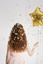 Back view of redheaded young woman with star-shaped golden balloon under shower of confetti - ABIF00892