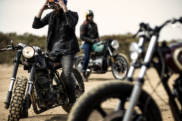 Three men sitting on cafe racer motorcycles on a dusty dirt road. - MINF07948