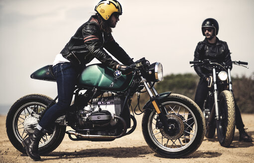 Side view of man wearing crash helmet sitting on cafe racer motorcycle on a dusty dirt road. - MINF07951