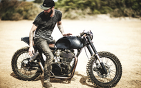 Side view of bearded man with tattoos on his arms sitting on cafe racer motorcycle on a dusty dirt road. - MINF07954