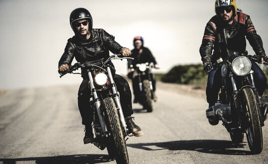 Three men wearing open face crash helmets and sunglasses riding cafe racer motorcycles along rural road. - MINF07957