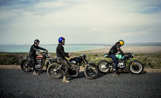 Three men wearing open face crash helmets sitting on cafe racer motorcycles on a rural road. - MINF07960
