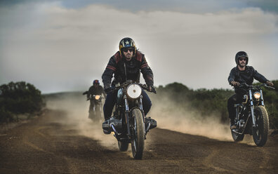 Three men riding cafe racer motorcycles along dusty dirt road. - MINF07963