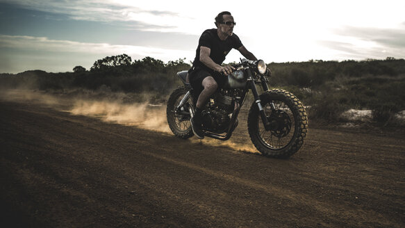 Man wearing shorts and sunglasses riding cafe racer motorcycle on a dusty dirt road. - MINF07966