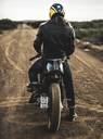 Rear view of man wearing crash helmet sitting on cafe racer motorcycle on a dusty dirt road. - MINF07969