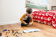 Boy with brown hair kneeling on hardwood floor in a nursery, playing with toy building bricks. - MINF07987