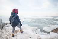 Rear view of boy wearing warm clothes standing on an icy ledge of a partially frozen lake. - MINF07996