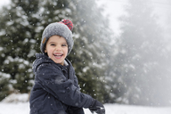 Smiling boy wearing grey knit hat standing outdoors in the snow, looking at camera. - MINF08002