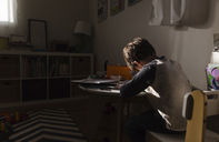 Rear view of boy with brown hair sitting indoors on a chair at a table, writing. - MINF08011