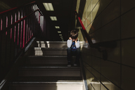 Boy with brown hair sitting in the shade on a staircase, head in hands. - MINF08014