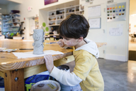 Boy with brown hair standing indoors, holding paintbrush, painting modelling clay object. - MINF08017