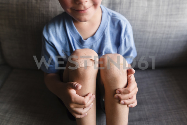 High angle view of boy wearing blue T-shirt sitting on a sofa, a plaster on his right knee. - MINF08020
