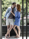 A couple standing on a balcony kissing. - MINF08068