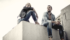 A low angle shot of a couple sitting on a city rooftop. - MINF08101