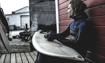 A surfer wearing a wetsuit sitting by a wooden building with a surfboard on his knees. - MINF08107