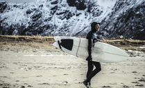 A surfer wearing a wetsuits and carrying a surfboard walking on a beach. - MINF08110