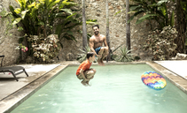 A man and boy in mid air, jumping into a swimming pool. - MINF08128