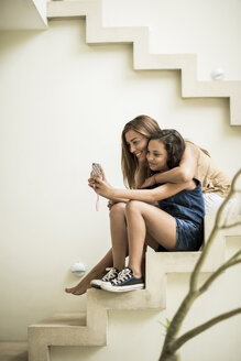 A woman and a girl sitting on outdoor steps looking at a mobile phone. - MINF08134
