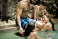 A family hugging in a swimming pool. - MINF08137