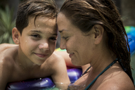 A woman and a boy cuddling in a swimming pool. - MINF08140