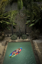 A girl with eyes closed lying on a pool raft in a swimming pool. - MINF08143