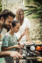 A family standing at a barbecue cooking food. - MINF08158