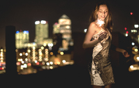 A young woman in a sequined dress dancing on a rooftop at night holding a party sparkler. - MINF08182