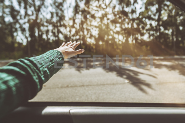 Hand of a woman leaning out of car window - KIJF01993