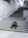 Black businessman taking a break for lunch sitting on a stairway step. - MINF08207