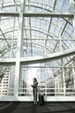 Businessman and woman meeting in a large glass covered walkway - MINF08213