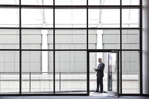 Businessman on a small office balcony checking his phone. - MINF08216
