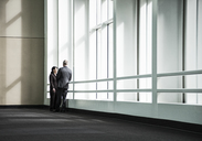 Businessman and woman meeting in a large glass covered walkway - MINF08219