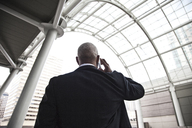 Black businessman on the phone while walking through a large glass covered walkway. - MINF08222