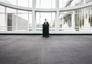 Businessman  at a podium with no one to talk to. - MINF08231
