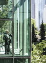 Businessman on the phone standing in a glassed in walkway. - MINF08234