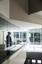 Businessman standing in a conference room window in a large business centre. - MINF08237