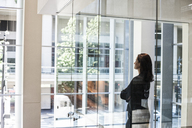 Businesswoman standing in a conference room window in a large business centre. - MINF08240