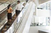 Businessman and woman on escalators and headed to a meeting in a business centre. - MINF08246