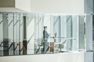 Businesswoman standing in a conference room window in a large business centre. - MINF08252