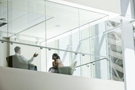 Businessman and woman standing behind a conference room window in large business centre. - MINF08255