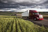 Commercial truck driving though wheat fields of eastern Washington, USA at sunset. - MINF08330