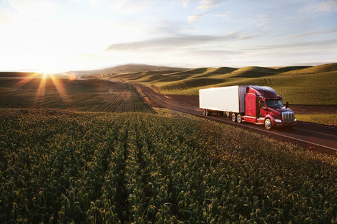 Peterbilt Class8 commercial truck driving through farmlands in eastern Washington, USA at sunset. - MINF08333