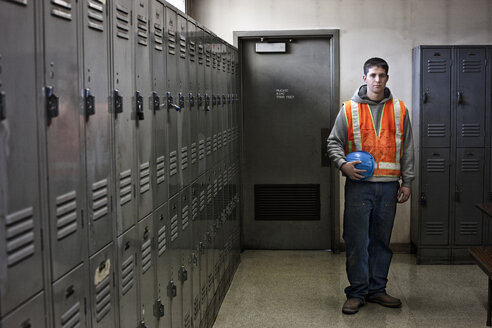 View of a young Caucasian factory worker wearing a safety vest and standing next to lockers in a factory break room. - MINF08366