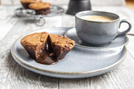 Chocolate muffin with liquid chocolate on plate with coffee cup - SARF03894