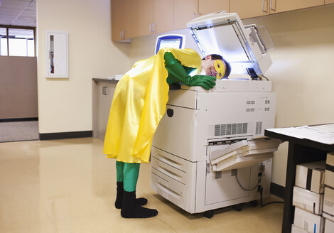 Caucasian businessman office super hero stands at photocopier, making copy of his head. - MINF08462