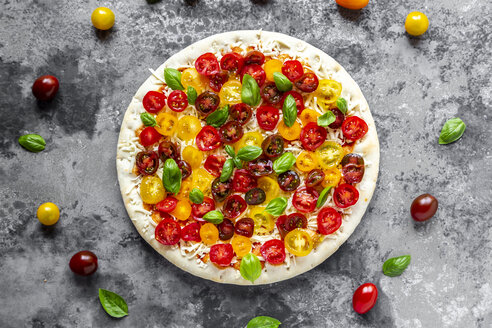 Unbaked pizza with tomatoes and basil leaves - SARF03897