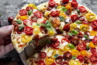 Hand holding slice of pizza with tomatoes and basil leaves - SARF03900
