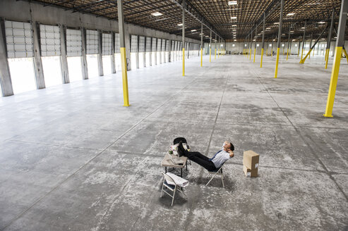 Caucasian man sitting with feet up on desk  in front of loading dock doors in a new warehouse interior. - MINF08563