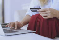 Blond woman sitting on couch, using laptop to make a payment with her credit card - AZF00071