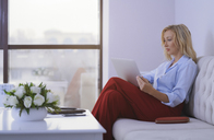 Blond woman sitting on couch, using laptop - AZF00074